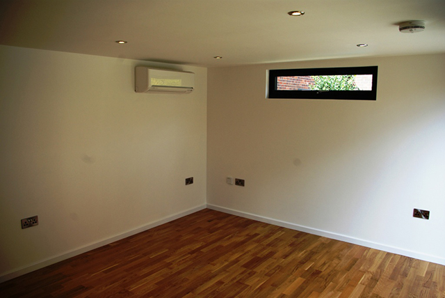 The interior has a light modern feel. The air conditioning unit sits discreetly in the corner of the room.