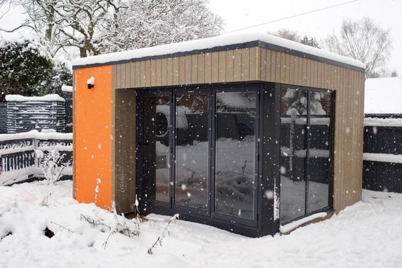 The orange rendered panel makes this garden room pop, even in the snow