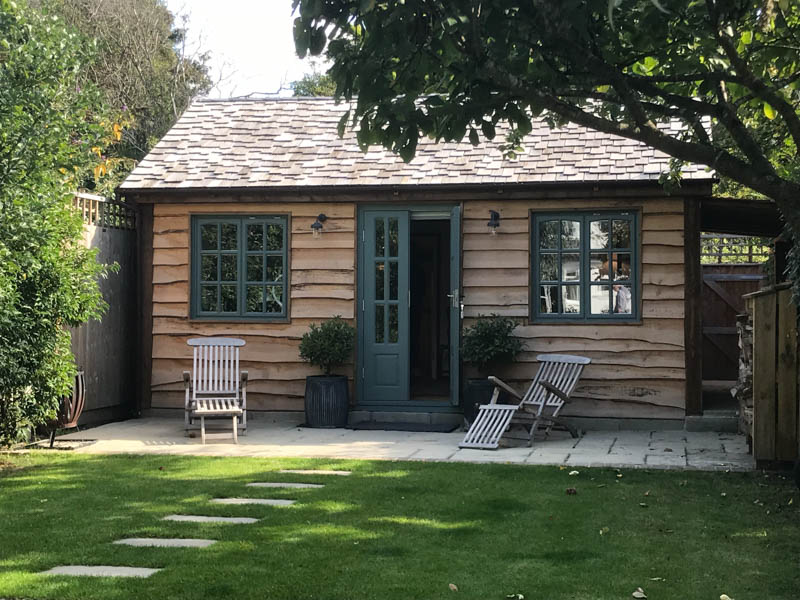 The cottage features a beautifully tiled roof and waney edge larch cladding.