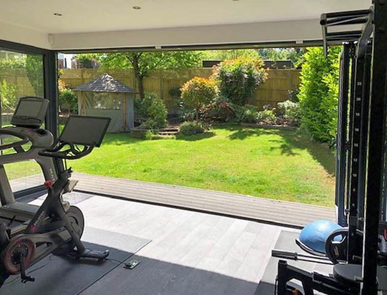 Bi-fold doors fold up to open the gym out onto then garden
